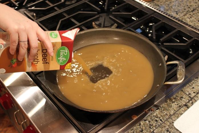 Adding beef broth to pan