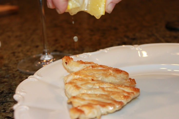 A squeeze of lemon over some chicken paillard