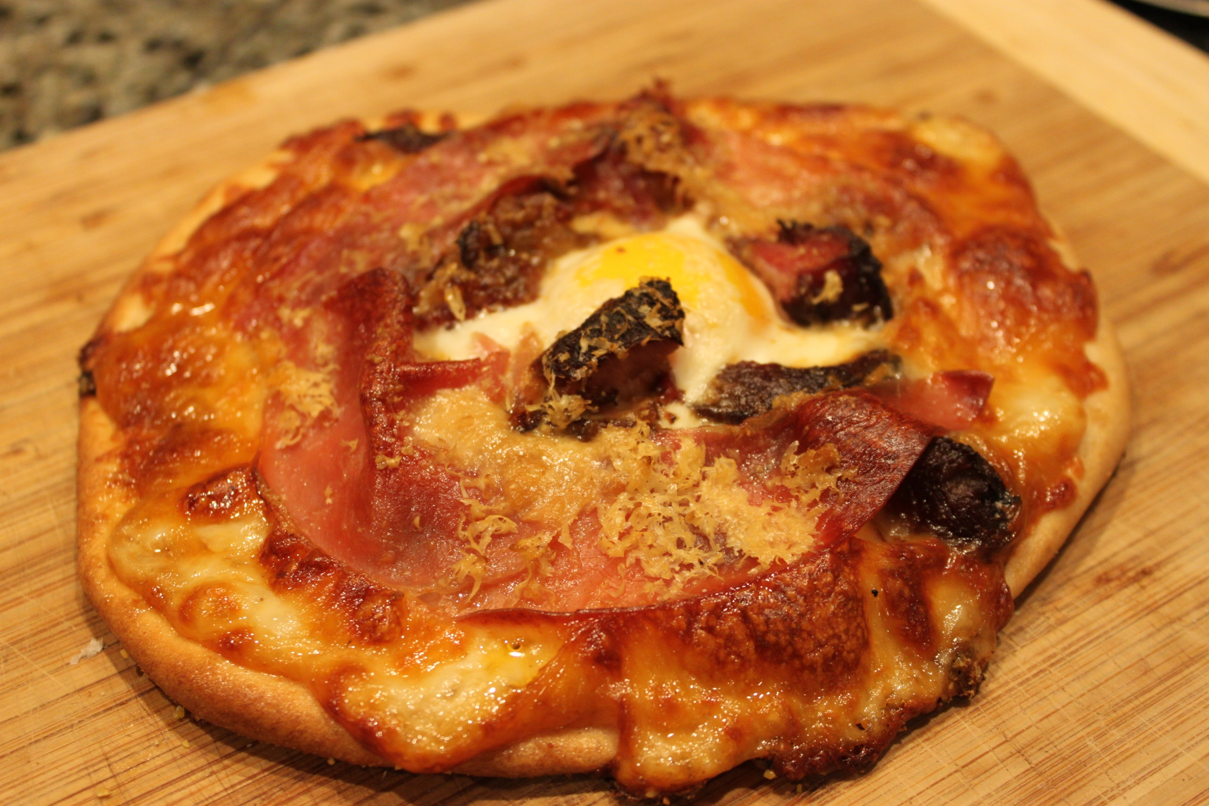 pizza with egg, prosciutto, ham and cheese with gravy