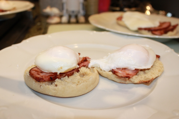 english muffin stacked with ham and poached egg