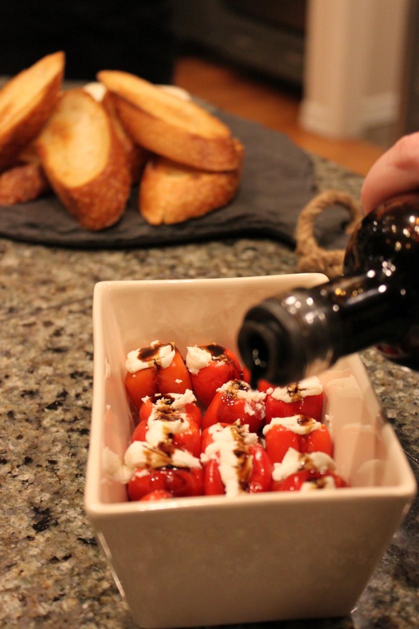 drizzling balsamic vinegar onto stuffed peppadews